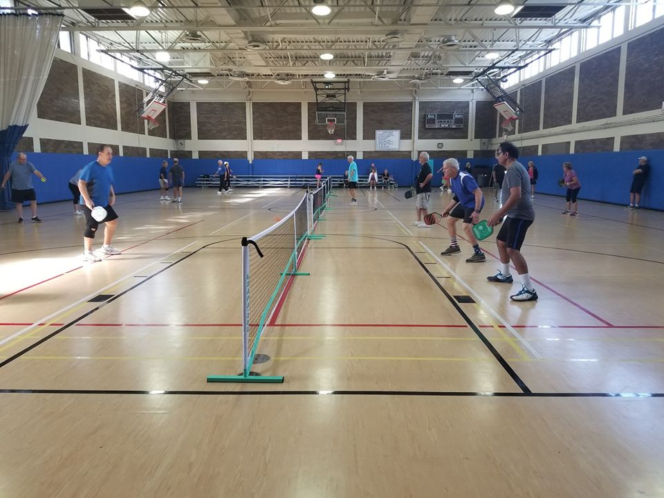 Men and women are playing pickleball inside the arlington park gymnasium. They are actively hitting the ball back and forth over a net.