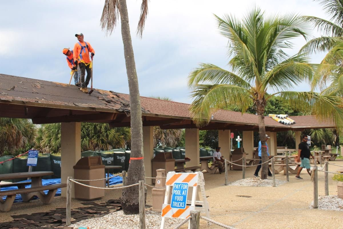 A roofing contractor started removing the old shingles from the lido pavilion. Two men dressed in orange construction uniforms standing on the roof of the lido pavilion removing shingles.