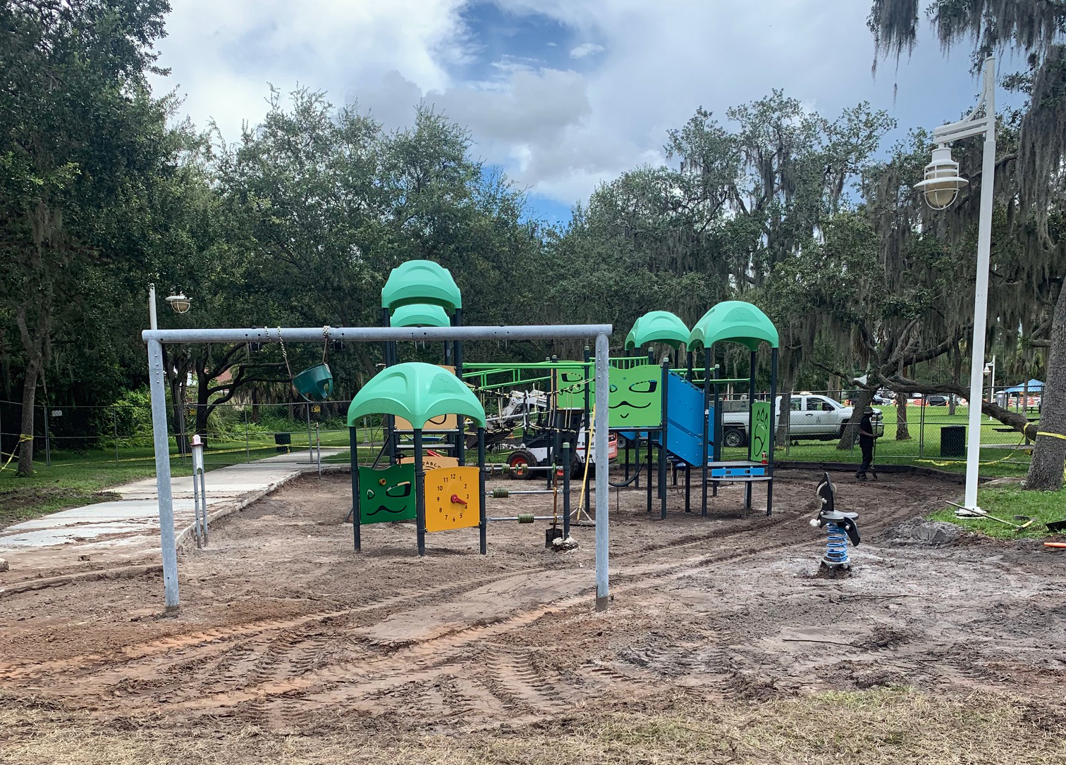 Playground with surface removed on the ground with dirt. Playground is yellow blue green and black with a slide and swings on a cloudy day.