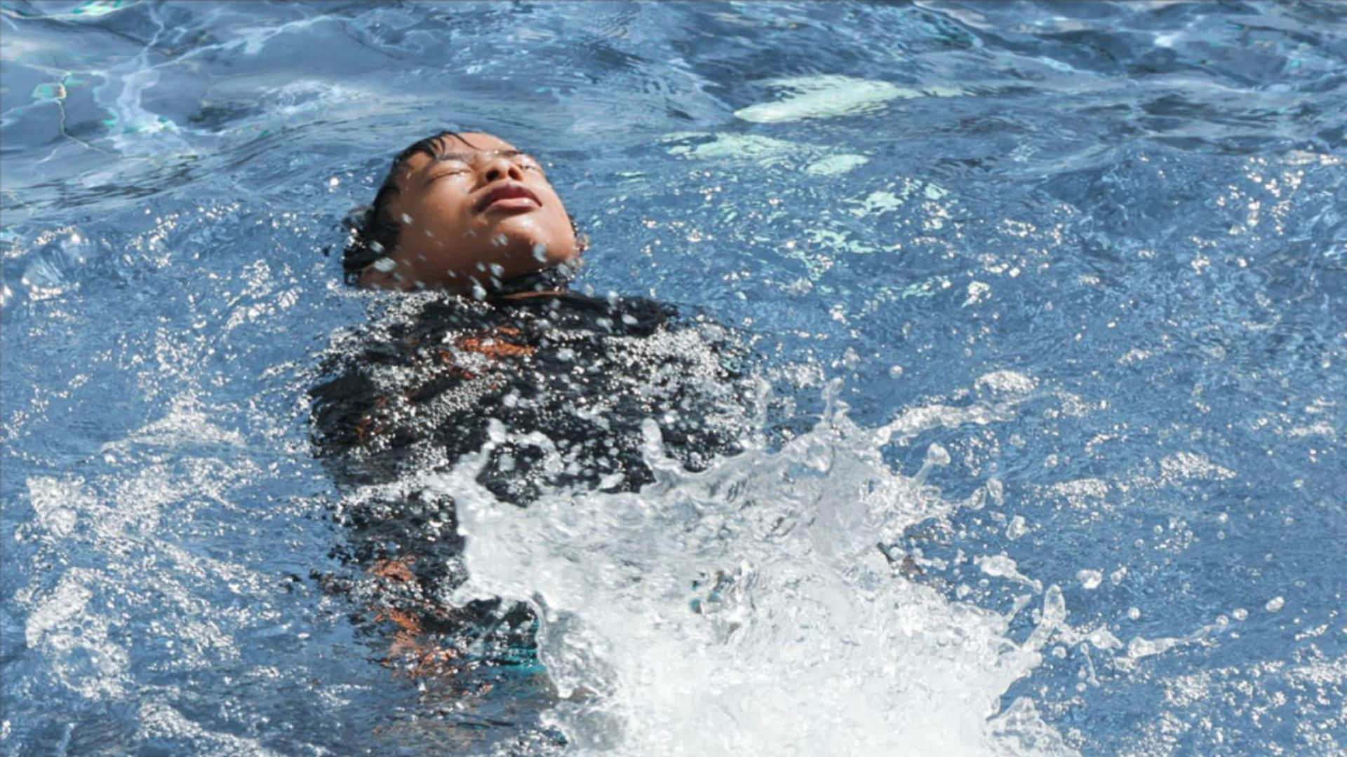 a little boy wearing a black shirt is swimming on his back