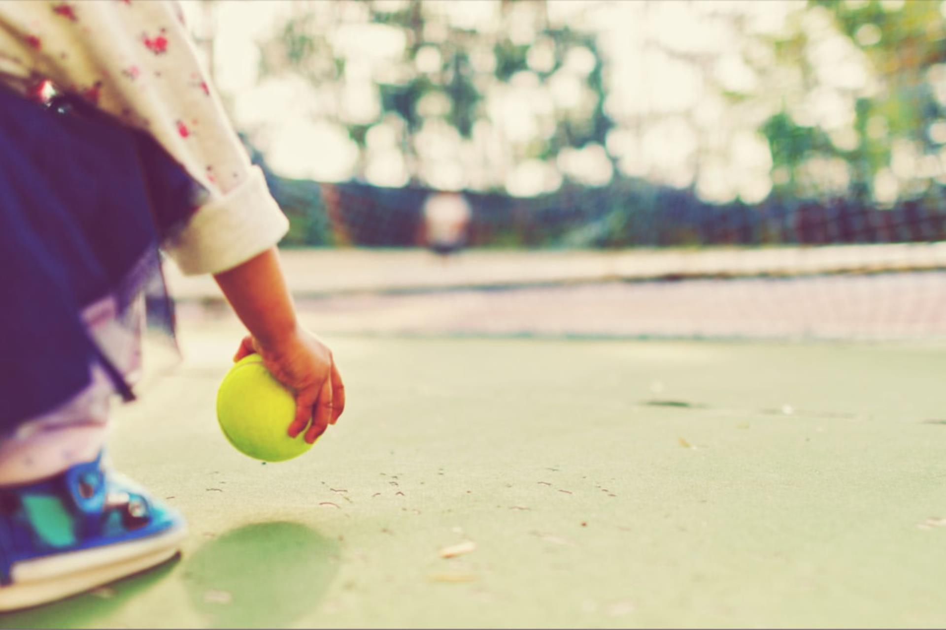 A toddler bends down to pick up a tennis ball on the tennis court.