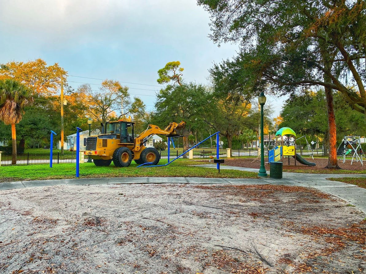 Construction truck is taking down the metal poles of the shade structure. The location is mary dean park on a cold winter morning.