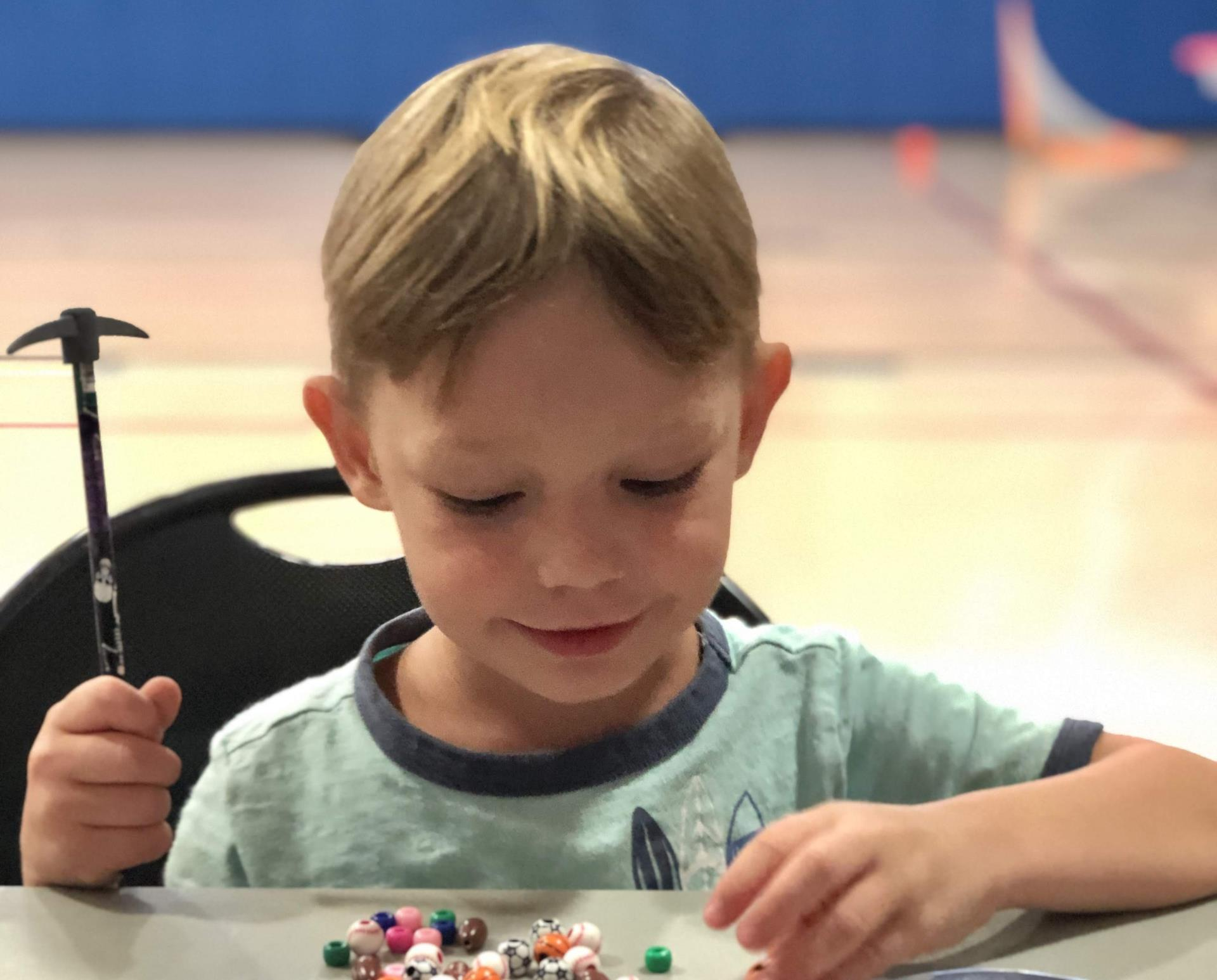 A little boy sits in the gym making beaded bracelets with a smile on his face